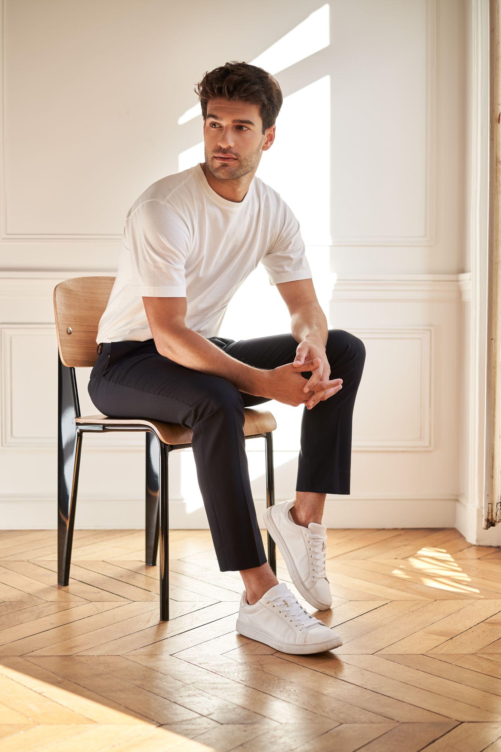Lautrec_T-Shirt blanc coton bio GOTS et Pantalon Ville laine éthique_portés par Manu Noraced assis sur une chaise design devant un mur blanc