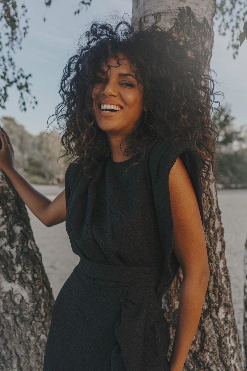 MAISON-PEOPLE_ Robe Lison epaulettes noir volants en bas de robe manches courtes tissu tweed coton upcycling porte par Juliana mannequin bresilienne vue de face - photo prise a la f
